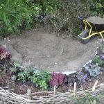 Nachdem wir die Pflanzen im vorderen Bereich eingesetzt haben, heben wir die Grube im Zentrum aus. Da wir hier eine Erhöhung des Beetes erreichen wollen, reichen 20 cm Tiefe.